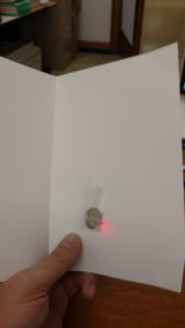 LED pushed through card holes with battery attached.